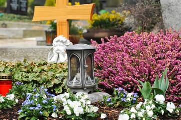 Metall-Urne auf einem Grab mit Zierpflanzen-Dekoration