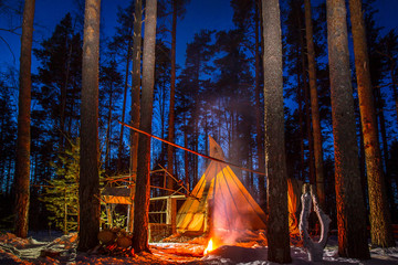 The wigwam in the evening forest. A fire on the background of the Wigwam. Night forest. Construction in the forest.