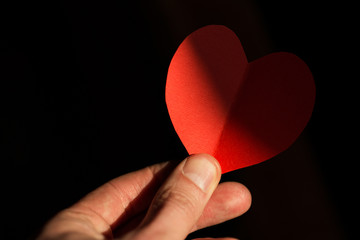 Red heart made of paper on which a shadow falls in the hand of a young man on a black background.