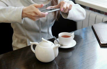 Unrecognizable woman's hands pictures of teapot and Cup in a cafe on her cell phone. Side view.