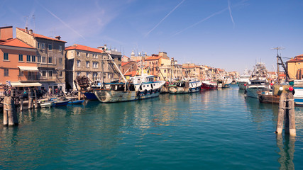 Fishing boats moored in a canal in Chioggia, Italy.