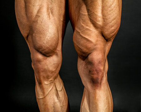 Detail of male bodybuilder front leg muscles on black background. Quadriceps and tibialis anterior.