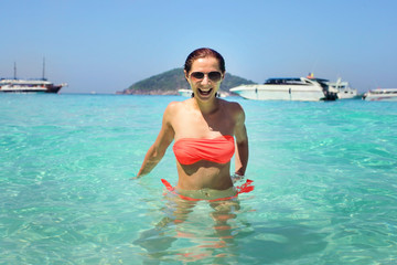 Young woman with sunglasses in crystal clear sea water with smiling happy face  expression. Similan Islands, Thailand