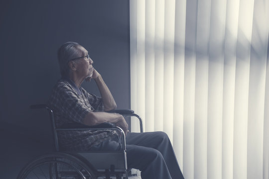 Sad lonely senior man sitting on wheelchair