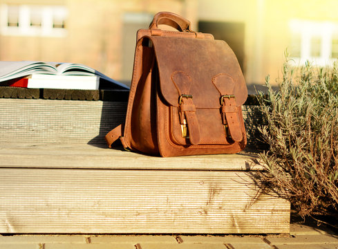 vintage natural leather backpack and books on gray rustic wooden stairs