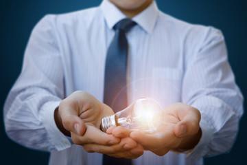 Businessman holding a burning lamp.
