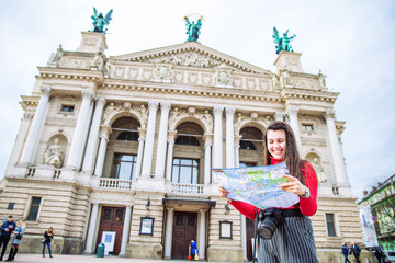 tourist woman with map stand in front of old european building. travel concept. copy space