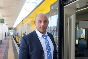 The train conductor on the platform next to the train