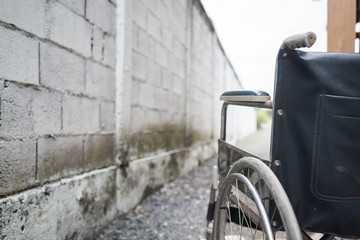 Close up wheelchair outdoor with concrete wall.