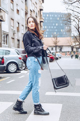 fashion blogger outfit details. fashionable woman wearing ripped vintage denim jeans, suede jacket, black biker boots -ankle shoes and black trendy handbag. detail of a perfect fall fashion outfit.