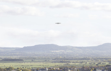 UFO Sighting, flying saucer in the sky over a town, metallic reflective craft
