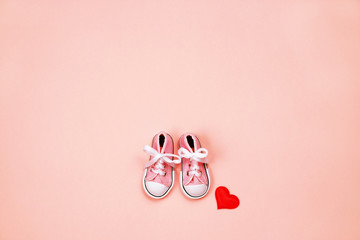 Baby sneakers on pink background
