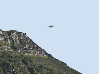 UFO Sighting, flying saucer in the sky over hills on summers day, metal flying spacecraft