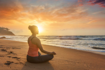 Woman doing yoga oudoors at beach - Padmasana lotus pose