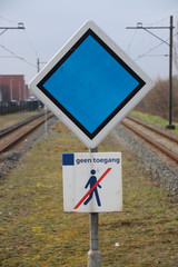 sign with stop advice for train and no trespassing sign in the middle of 2 platforms on the station of Waddinxveen, The Netherlands