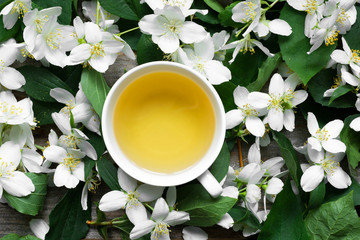 Cup of green jasmine tea on jasmine flowers background
