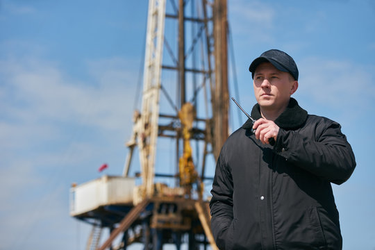 Security guard using portable wireless transceiver. Security man with walkie talkie, standing outdors against oil drilling station platform, safety concept