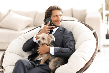successful businessman holds his dog and pet and talks on the smartphone
