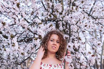 Beautiful curly woman enjoying smell flowering near the cherry tree.