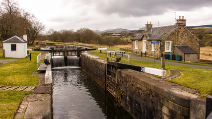 Water flowing over a closed canal lock gate.