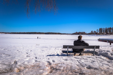 Mora - March 30, 2018: Local swede by the frozen lake in the town of Mora in Dalarna, Sweden