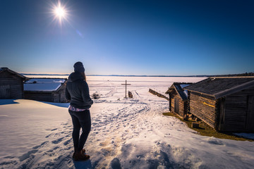 Rattvik - March 30, 2018: Traveler by the frozen lake Siljan in Rattvik, Dalarna, Sweden