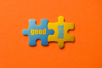 Wall Mural - Two colored details of puzzle with text good luck on orange background, Yellow and Blue, close up.