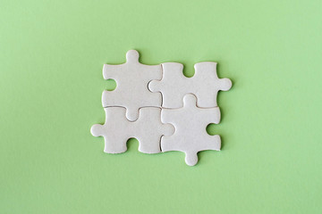 Wall Mural - four white details of puzzle on green pastel background