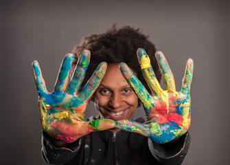 happy black woman with her hands painted on a gray background