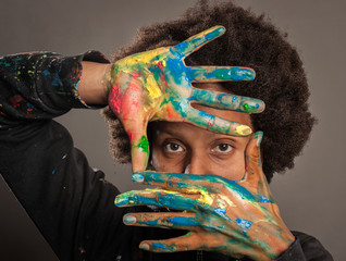 black woman with her hands painted on a gray background