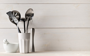 Kitchen cooking utensils in white cup with pestle and mortar on white table