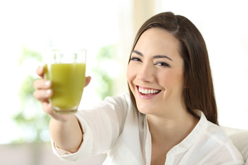Satisfied woman showing a glass of vegetable juice