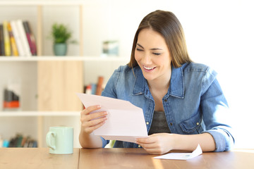 Happy woman reading a letter at home