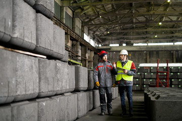 Full length portrait of two workers walking across workshop in modern industrial plant, copy space