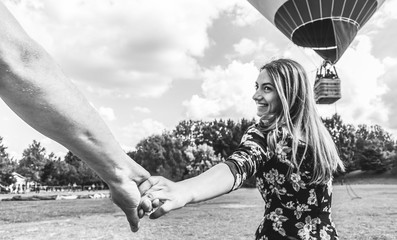 Happy young woman wants to make balloon tour holding boyfriend's hand - Follow me, travel and love concept - Couple of lovers having fun in summer vacation - Black and white editing