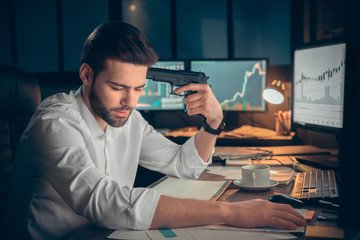 Young male trader at office work concept sitting holding gun