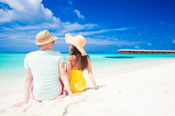 back view of couple sitting on a tropical beach on Maldives