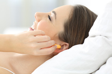 Woman covering ears using plugs on the bed