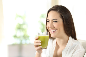 Woman drinking a vegetable juice looking away