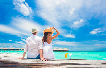 back view of couple sitting on wooden bridge by tropical beach on Maldives
