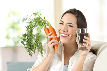 Woman showing healthy carrots and water glass