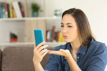 Woman sending a kiss online with a phone