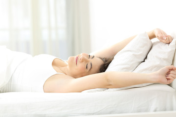 Woman stretching arms in the moring on the bed