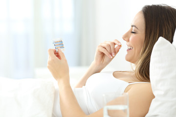 Woman taking contraceptive pill in the bed