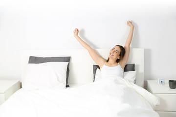 Woman waking up raising arms on the bed
