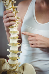 Female physiotherapist pointing at spine model