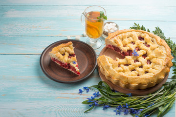 Homemade pie with flowers and tea on a wooden background. With an empty place for the inscription.