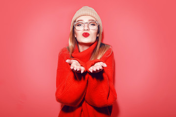 Happy Smiling Hipster Girl kiss in knitted red sweater and hat having fun . Cute girl in glusses with piercing in the nose.