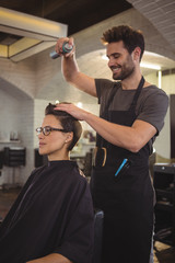 Male hairdresser styling customers hair