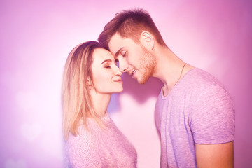 Close-up of beautiful couple kissing. Happy man and girl touching with their noses in pink background. Portrait of a loving. Kiss, romance.